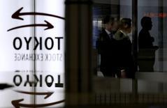Люди проходят мимо логотипа Токийской фондовой биржи  30 января 2014 года. Азиатские фондовые рынки завершили торги понедельника разнонаправлено под влиянием событий в Ираке и локальных новостей. REUTERS/Toru Hanai