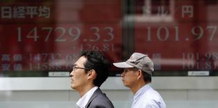 Un hombre camina frente a una pantalla electrónica afuera de una volsa de valores en Tokio, 27 de mayo de 2014. El índice Nikkei de la bolsa de Tokio cayó el lunes a un mínimo en dos semanas luego de que los avances de la insurgencia en Irak aumentaron el temor a una interrupción potencial de sus exportaciones de petróleo.     REUTERS/Toru Hanai