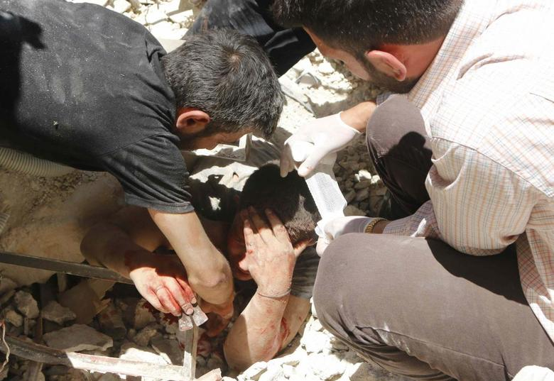A man tries to pull a casualty from under the rubble of collapsed buildings at a site hit by what activists said was a barrel bomb dropped by forces loyal to Syria's President Bashar al-Assad in Aleppo's district of al-Sukari June 16, 2014.  REUTERS/Hosam Katan