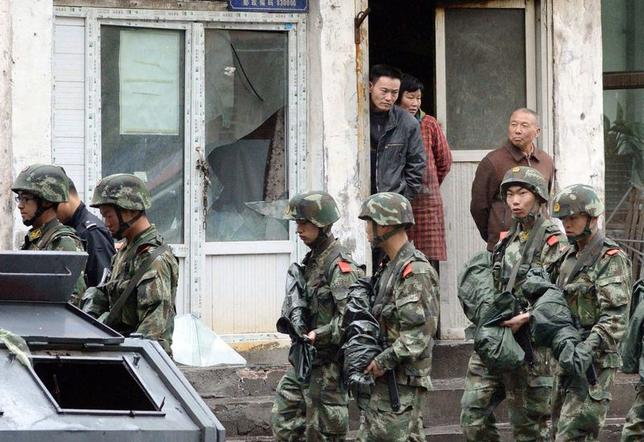 Paramilitary policemen patrol past a building, where a window was damaged by an explosion in Urumqi on Thursday, in the Xinjiang Uighur Autonomous Region, in this photo taken by Kyodo on May 22, 2014.  REUTERS/Kyodo/Files
