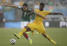 Jogador mexicano Hector Herrera (esquerda) disputa bola com o camaronês Alexandre Song durante partida na Arena das Dunas, em Natal. 13/6/2014 REUTERS/Toru Hanai
