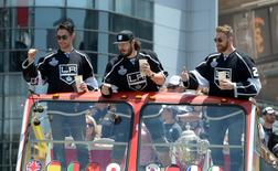 Los Angeles Kings players Alec Martinez (27), Drew Doughty (8) and Trevor Lewis (22) wave to the crowd during a parade on Figueroa Street to celebrate winning the 2014 Stanley Cup. Mandatory Credit: Kirby Lee-USA TODAY Sports