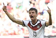 Игрок сборной Германии Томас Мюллер празднует гол в ворота Португалии в Салвадоре 16 июня 2014 года. Сборная Германии в понедельник забила четыре безответных мяча в ворота португальцев в своем юбилейном - сотом - матче на мировых первенствах, а команда США вырвала победу у Ганы. REUTERS/Dylan Martinez