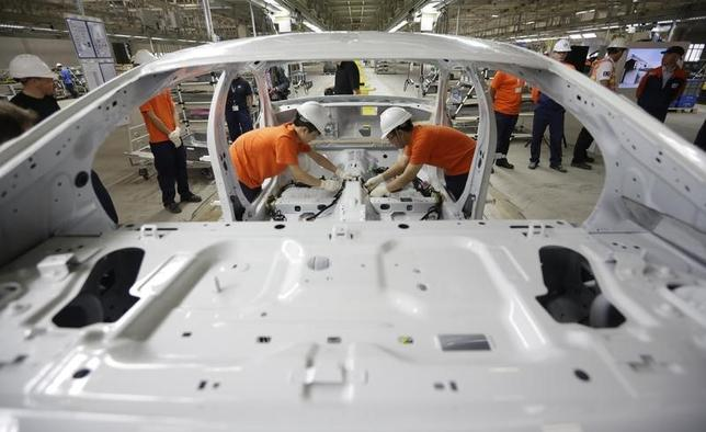 Workers assemble parts of a Volvo car at an assembly line of the new Volvo automobile manufacturing plant in Chengdu, Sichuan province, June 5, 2013.  REUTERS/Jason Lee