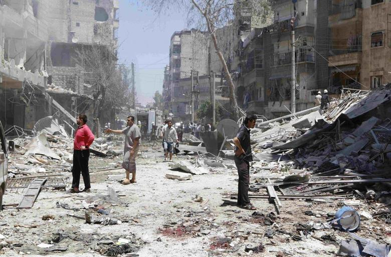 People inspect a site hit by what activists said was a barrel bomb dropped by forces loyal to Syria's President Bashar al-Assad in Aleppo's district of al-Sukari June 16, 2014. REUTERS/Hosam Katan