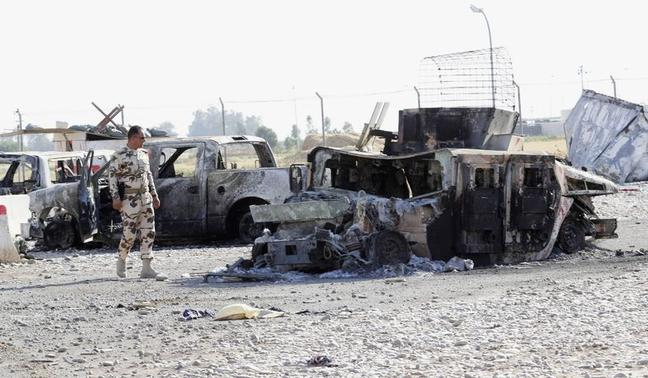 A member of the Kurdish security forces looks at the wreckage of a vehicle belonging to Iraqi security forces in the outskirts of Kirkuk June 16, 2014. REUTERS/ Ako Rasheed