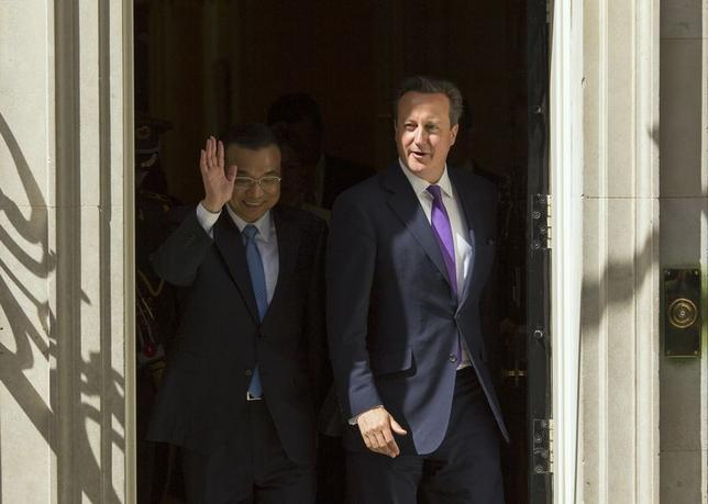Chinese Premier Li Keqiang waves as he leaves Number 10 Downing Street with Britain's Prime Minister David Cameron, to walk to the Foreign Office in London June 17, 2014.     REUTERS/Kieran Doherty