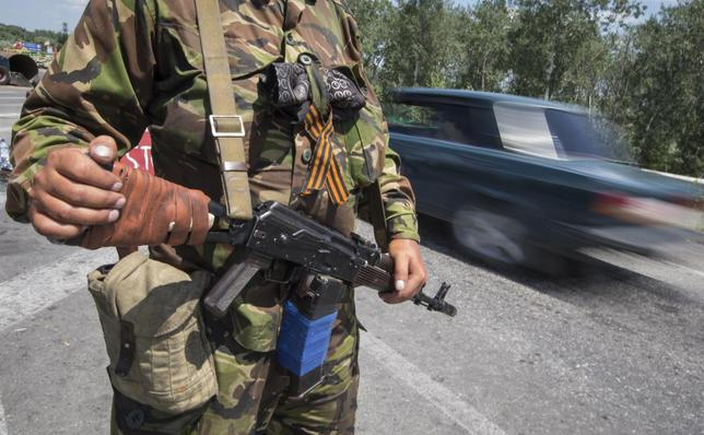 An armed pro-Russian separatist with attached orange ribbon of St. George, a symbol widely associated with pro-Russian protests in Ukraine, stands guard at a road check point outside the eastern Ukrainian city of Luhansk June 8, 2014. REUTERS/Shamil Zhumatov