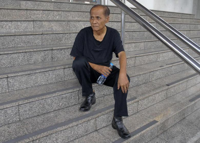 Chalad Vorachat, a retired navy lieutenant and serial hunger striker, sits on the steps of the criminal court in Bangkok June 10, 2014. REUTERS/Stringer