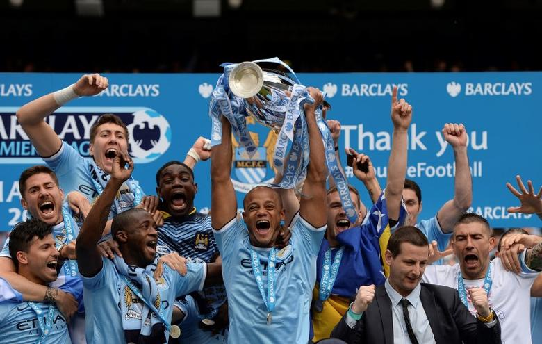 Manchester City's captain Vincent Kompany celebrates after winning the English Premier League trophy following their soccer match against West Ham United at the Etihad Stadium in Manchester, northern England May 11, 2014. REUTERS/Nigel Roddis