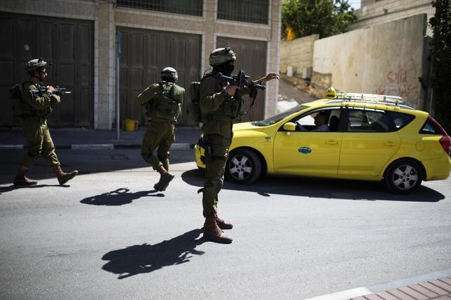 Israeli soldiers take part in an operation to locate three Israeli teens in the West Bank City of Hebron June 17, 2014. REUTERS/Amir Cohen