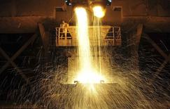 A labourer guides as slag is poured into a container at Dongbei Special Steel Group Co. Ltd. in Dalian, Liaoning province December 27, 2013. REUTERS/China Daily