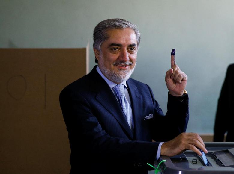 Afghan presidential candidate Abdullah Abdullah holds up his ink-stained finger as he casts his vote at a polling station in Kabul June 14, 2014. REUTERS/Ahmad Masood