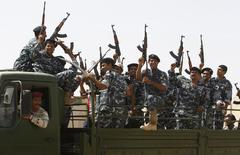 Shiite volunteers, who have joined the Iraqi army to fight against the predominantly Sunni militants from the radical Islamic State of Iraq and the Levant (ISIL) who have taken over Mosul and other northern provinces, gesture with their weapons in Baghdad, June 18, 2014. The United States is contemplating talks with its arch-enemy Iran to support the Iraqi government in its battle with Sunni Islamist insurgents who routed Baghdad's army and seized the north of the country in the past week.  REUTERS/Ahmed Saad (IRAQ - Tags: CIVIL UNREST POLITICS MILITARY)