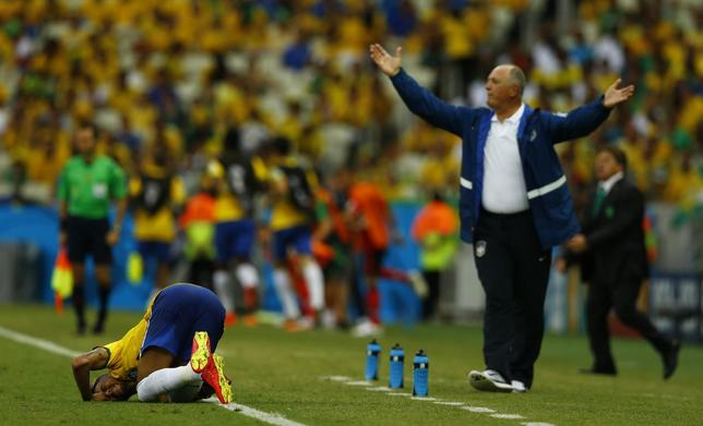 Brazil's coach Luiz Felipe Scolari (R) reacts as Neymar lies on the pitch after a challenge during their 2014 World Cup Group A soccer match against Mexico at the Castelao arena in Fortaleza June 17, 2014. REUTERS/Marcelo Del Pozo