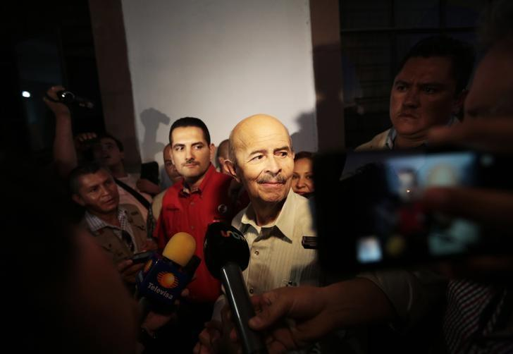 Michoacan's Governor Fausto Vallejo (C) walks surrounded by the media while visiting a townhouse in Apatzingan January 14, 2014. REUTERS/Jorge Dan Lopez
