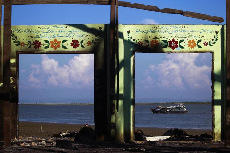 A boat is framed by the ruins of a destroyed mosque in a part of Pauktaw township that was burned in recent violence, in this October 27, 2012 file picture.    REUTERS/Soe Zeya Tun