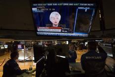 A Wall Street, des traders regardent la retransmission de la conférence de presse de la présidente de la Réserve fédérale des Etats-Unis Janet Yellen. La Fed a laissé entendre mercredi qu'elle pourrait relever les taux d'intérêt à un rythme un peu plus soutenu à partir de l'année prochaine mais aussi que son taux des Fed funds - son principal taux directeur - pourrait se situer à long terme en deçà de ce qu'elle avait précédemment anticipé. /Photo prise le 18 juin 2014/REUTERS/Brendan McDermid