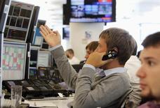 """Трейдеры в торговом зале инвестбанка Ренессанс Капитал в Москве 9 августа 2011 года. Риторика ФРС США придала импульс рискованным активам на мировых площадках и российскому рынку в частности, поспособствовав продолжению роста индексов, несмотря на убежденность трейдеров в """"перекупленности"""" акций. REUTERS/Denis Sinyakov"""