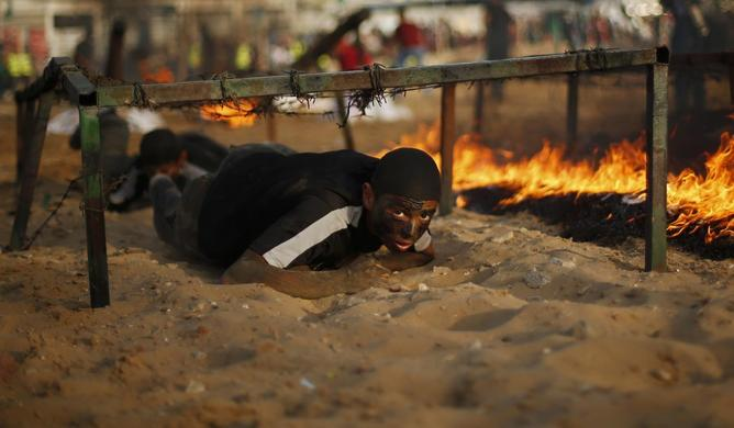 A young Palestinian crawls under an obstacle during a military-style graduation ceremony at Fajer Al-Entesar (dawn of victory) summer camp, organised by the Hamas movement, in Gaza City, June 19, 2014.REUTERS-Mohammed Salem