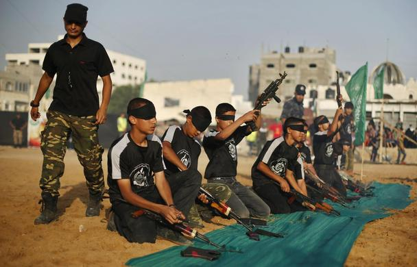 Blindfolded young Palestinians dismantle weapons during a military-style graduation ceremony at Fajer Al-Entesar (dawn of victory) summer camp, organised by the Hamas movement, in Gaza City, June 19, 2014. REUTERS-Mohammed Salem