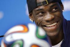 Italy's national soccer team player Mario Balotelli smiles while answering a question during an news conference at the Pernambuco arena in Recife, June 19, 2014.    REUTERS/Brian Snyder