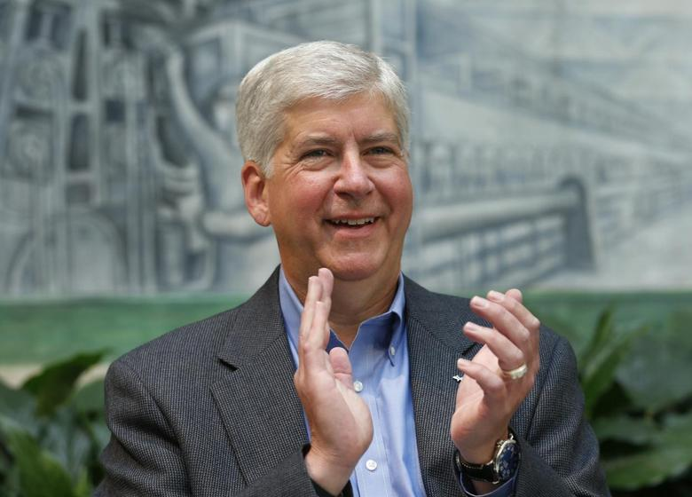 Michigan Governor Rick Snyder claps during a news conference to announce foundation pledges to the Detroit Institute of Arts in Detroit, Michigan June 9, 2014. REUTERS/Rebecca Cook
