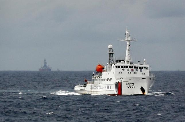A Chinese Coast Guard vessel (R) passes near the Chinese oil rig, Haiyang Shi You 981 (L) in the South China Sea, about 210 km (130 miles) from the coast of Vietnam June 13, 2014. REUTERS/Nguyen Minh