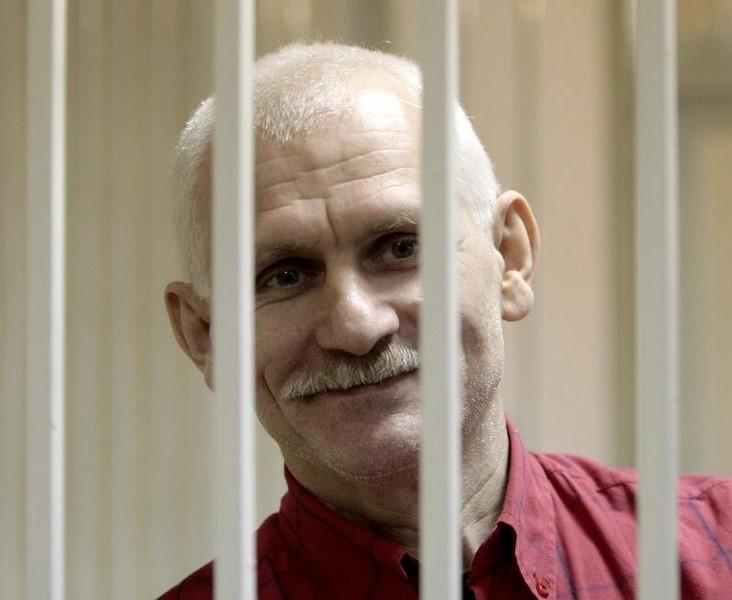 Human rights activist Ales Belyatsky smiles inside a guarded cage in a courtroom in Minsk November 24, 2011. REUTERS/Vasily Fedosenko