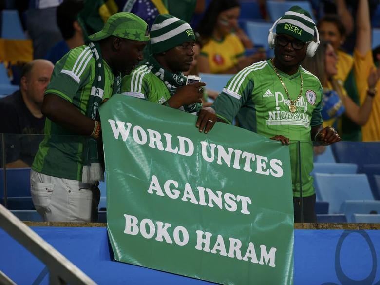 Nigerian fans hold a banner against Boko Haram during their 2014 World Cup Group F soccer match agaisnt Bosnia at the Pantanal arena in Cuiaba June 21, 2014. REUTERS/Michael Dalder