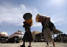 Farmers carry barrels at a fuel station during a diesel shortage in Sanaa January 8, 2014.   REUTERS/Mohamed al-Sayaghi