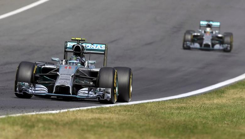 Mercedes Formula One driver Nico Rosberg of Germany is followed by team mate Mercedes Formula One driver Lewis Hamilton of Britain (R) during the Austrian F1 Grand Prix at the Red Bull Ring circuit in Spielberg June 22, 2014. REUTERS/Bernadett Szabo