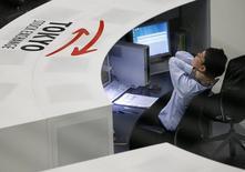 Сотрудник Токийской фондовой биржи за работой 11 апреля 2014 года. Японский индекс Nikkei поднялся на 0,1 процента до пятимесячного максимума. REUTERS/Issei Kato