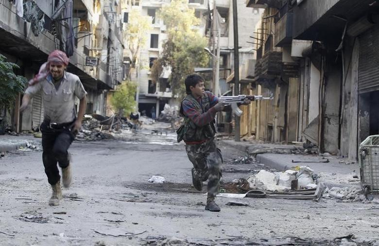 Mohammad (R), a 13 year-old fighter from the Free Syrian Army, aims his weapon as he runs from snipers loyal to the Syrian regime in Aleppo's Bustan al-Basha district October 29, 2013. REUTERS/Molhem Barakat