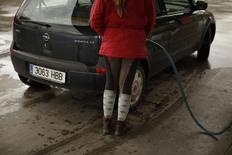 En la imagen, una conductora recarga su vehículo con gasolina en Cuevas del Becerro, cerca de Málaga, 4 de marzo de 2011. El precio del crudo Brent se mantenía cerca de los 115 dólares por barril el lunes, apuntalado por el temor a posibles cortes en el suministro desde Irak, donde el fin de semana la insurgencia suní tomó el control de bastiones a lo largo de la frontera con Siria.  REUTERS/Jon Nazca