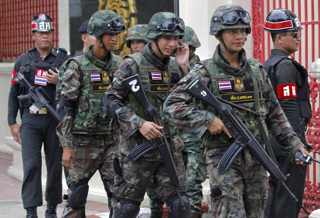 Soldiers patrol around the Royal Thai Army Headquarters as members of the Radio and Satellite Broadcasters gather in Bangkok June 18, 2014.   REUTERS/Chaiwat Subprasom