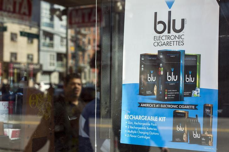 A man walks past an advertisement for e-cigarettes in New York April 24, 2014. REUTERS/Lucas Jackson