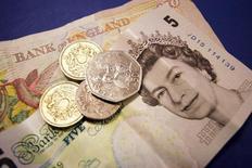 Банкноты и монеты британского фунта, 2 сентября 2005 года. Британский фунт снизился во вторник к доллару после того, как глава Банка Англии Марк Карни не смог укрепить надежды рынка на повышение ставки. REUTERS/Catherine Benson