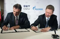 Глава OMV Герхард Ройсс и глава Газпрома Алексей Миллер подписывают договор о строительстве Южного потока в Вене 24 июня 2014 года. Российский госконцерн Газпром и австрийская OMV договорились инвестировать в строительство газопровода Южный поток на территории Австрии, которое оценивается в 200 миллионов евро, на паритете, сообщил глава австрийской компании Герхард Ройсс. REUTERS/Heinz-Peter Bader