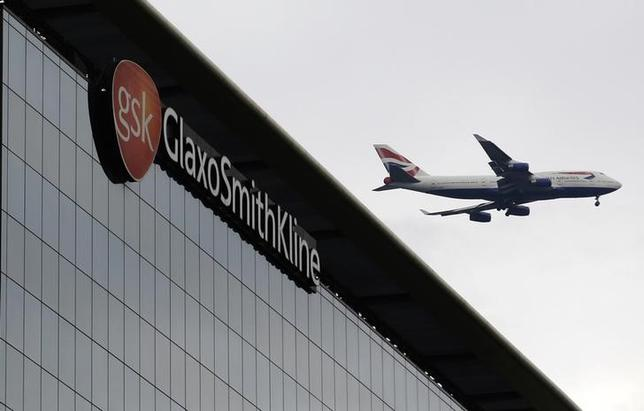 A British Airways airplane flies past a signage for pharmaceutical giant GlaxoSmithKline (GSK) in London April 22, 2014.REUTERS/Luke MacGregor