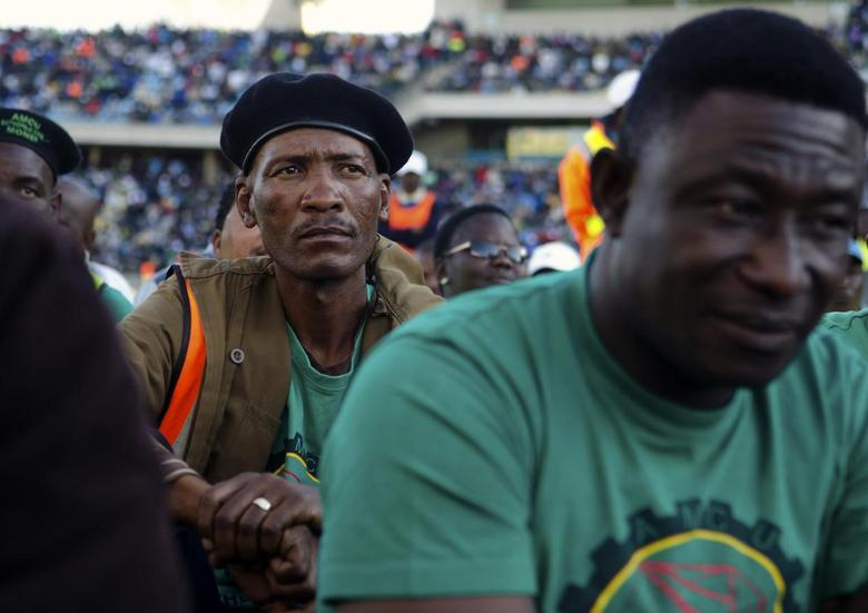 Members of the Association of Mineworkers and Construction Union (AMCU) listen as the union's President Joseph Mathunjwa (not seen) announces the end of the strike at the Royal Bafokeng Stadium in Rustenburg, June 23, 2014.  REUTERS/Skyler Reid
