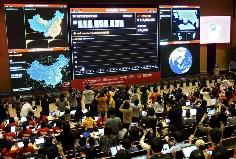 Employees and journalists take pictures and videos of a giant electronic board showing the online transaction value on Alipay, an online payment system of China's leading e-commerce retailers Taobao.com and Tmall.com, at the parent company Alibaba's headquarters in Hangzhou, Zhejiang province November 11, 2013. REUTERS/China Daily