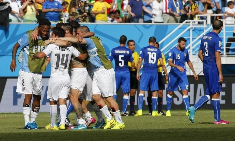 Uruguay players celebrate, while Italy players react, after their 2014 World Cup Group D soccer match at the Dunas arena in Natal June 24, 2014. REUTERS/Yves Herman