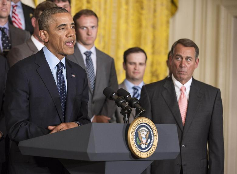 Speaker of the House John Boehner (R-OH), right, listens as U.S. President Barack Obama speaks during a ceremony honoring the President's Cup golf teams in the East Room of the White House in Washington June 24, 2014. REUTERS/Joshua Roberts