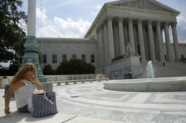 A woman uses her mobile phone at the plaza of the U.S. Supreme Court in Washington June 25, 2014.  REUTERS/Gary Cameron