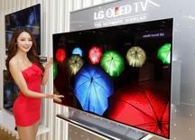 Una modelo posa junto a un televisor de diodos orgánicos que emiten luz (OLED) de LG Electronics en Seúl. 2 enero, 2013. LG Display Co considerará si realizará inversiones adicionales para aumentar la capacidad de inversión de las pantallas OLED plásticas para teléfonos y relojes inteligentes, dijo el presidente ejecutivo de la compañía. REUTERS/Lee Jae-Won