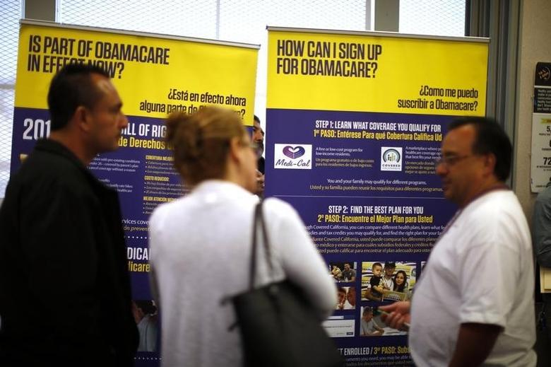 Julian Gomez (R) explains Obamacare to people at a health insurance enrolment event in Commerce, California March 31, 2014.  REUTERS/Lucy Nicholson