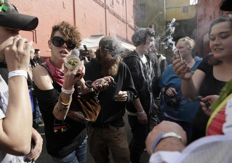 Participants smoke marijuana around 4:20 pm at the Seattle Hempfest 4/20 event in Seattle, Washington April 20, 2014. REUTERS/Jason Redmond
