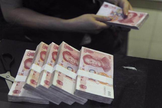An employee counts Chinese 100 yuan banknotes at a branch of China Merchants Bank in Hefei, Anhui province June 21, 2013. REUTERS/Stringer