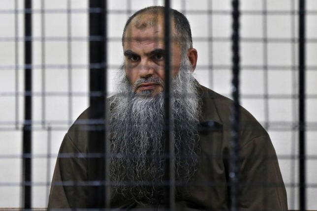 Radical Muslim cleric Abu Qatada looks on from behind bars at the State Security Court in Amman June 26, 2014. REUTERS/Muhammad Hamed